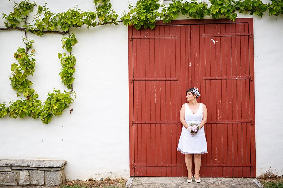 puerta roja y enredadera con la novia en un reportaje de pareja con fotografo de bodas en guipuzcoa