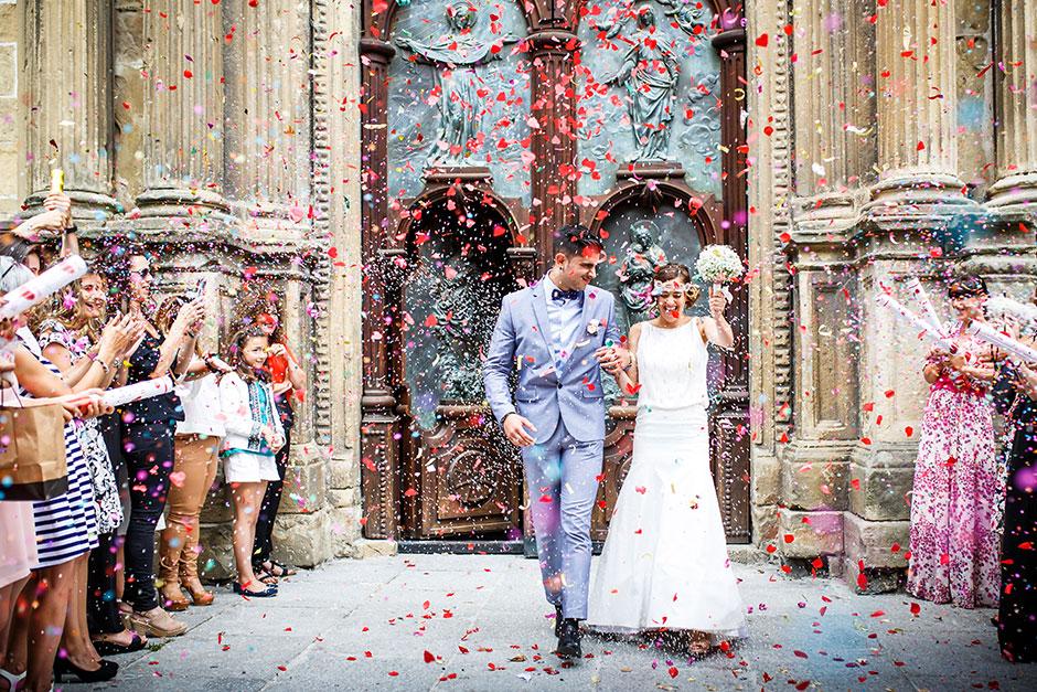 salida de una iglesia con mucho arroz y petalos en un reportaje de boda fotografo de bodas en guipuzcoa