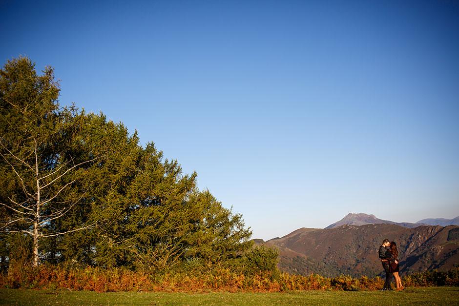pareja en monte en otoño con colores muy naranjas abrazo y beso