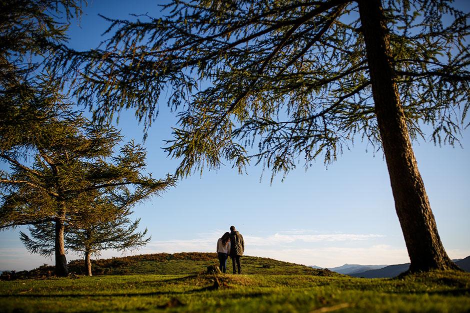 pareja de novios abrazados de espaldas observando el horizonte en el monte