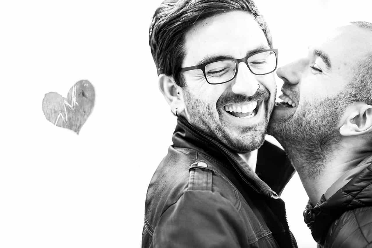 una pareja de chicos sonriendo cerca de un corazón pintado