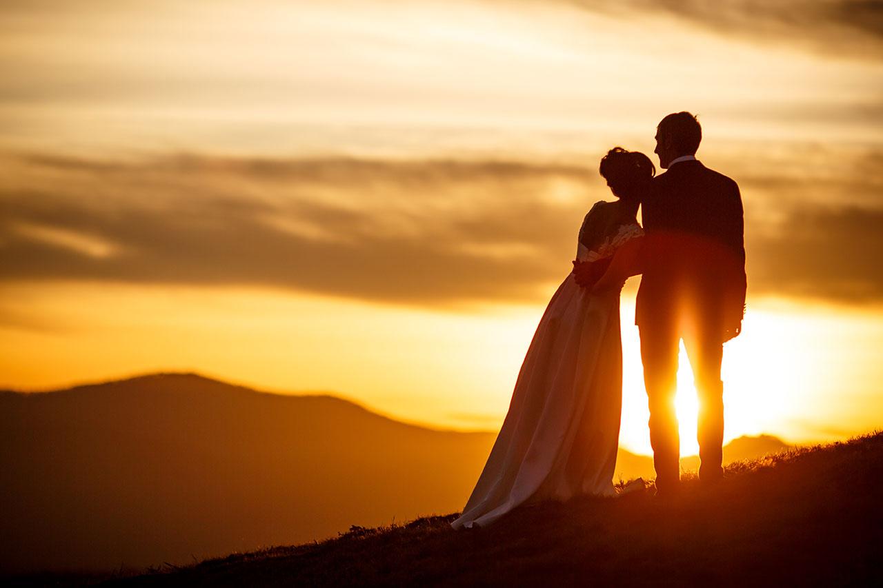 novia apoyada en su marido en pleno atardecer