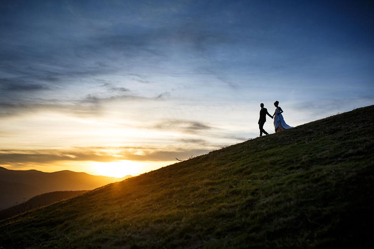 pareja de novios bajando por una ladera en pleno atardecer
