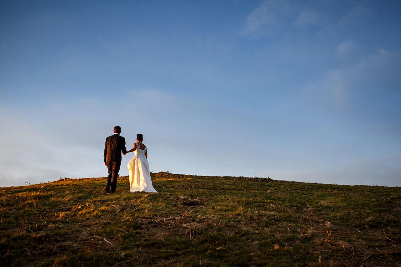 pareja subiendo una ladera en pleno atardecer