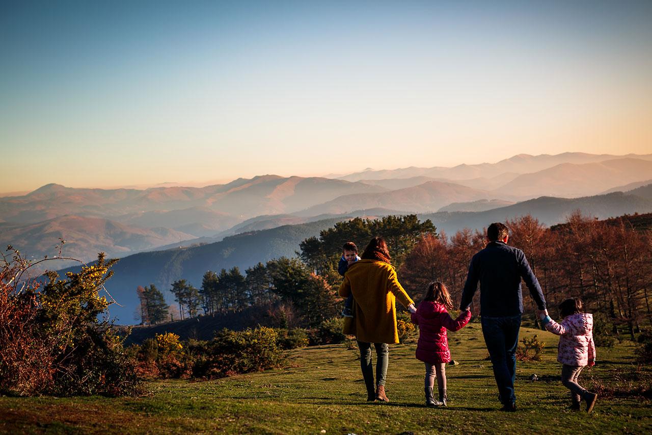 familia andado de espaldas por el monte en un reportaje de familia