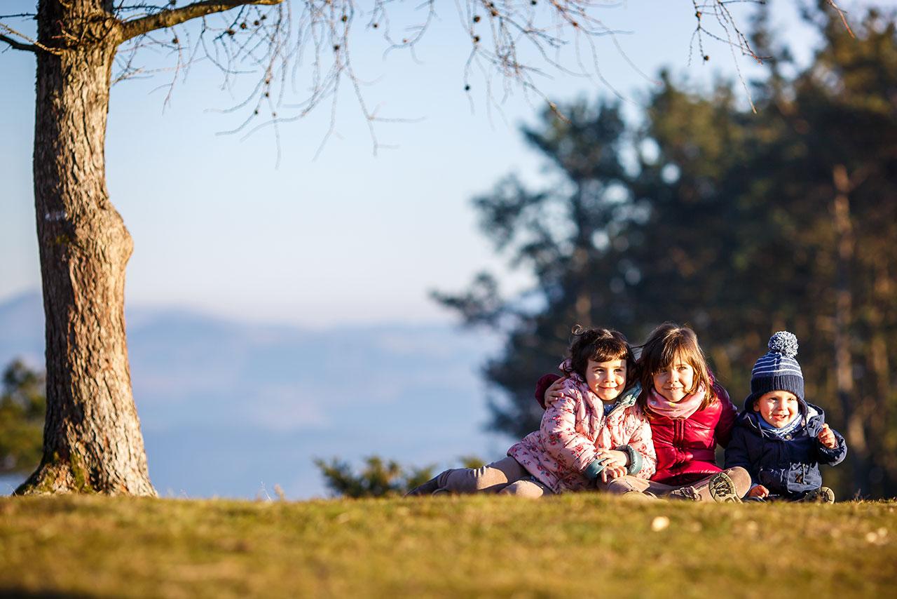 tres niños en el monte en un reportaje de familia sonriendo