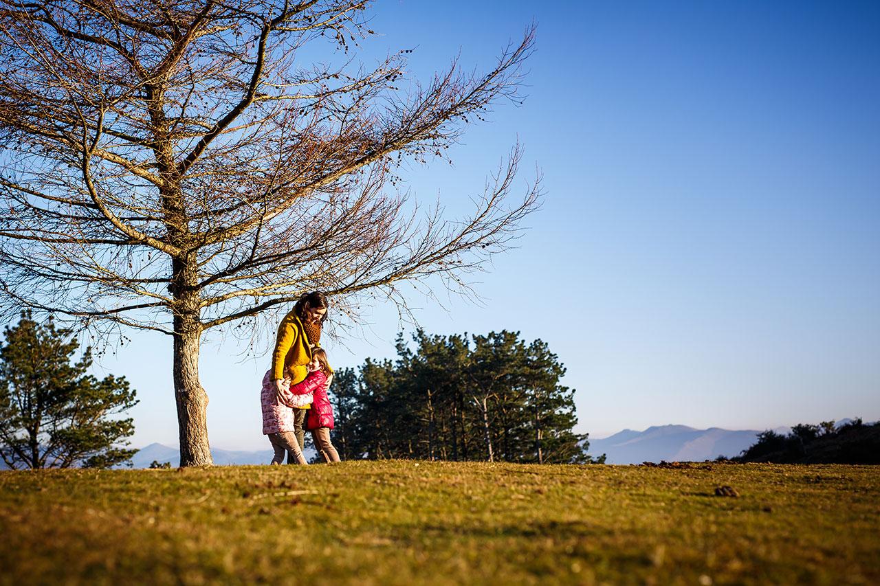 dos niñas abrazando a su madre en el monte en un reportaje en erlatz