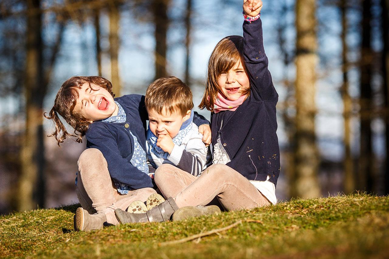 tres hijos de la familia imitando a un super héroe en un reportaje de familia