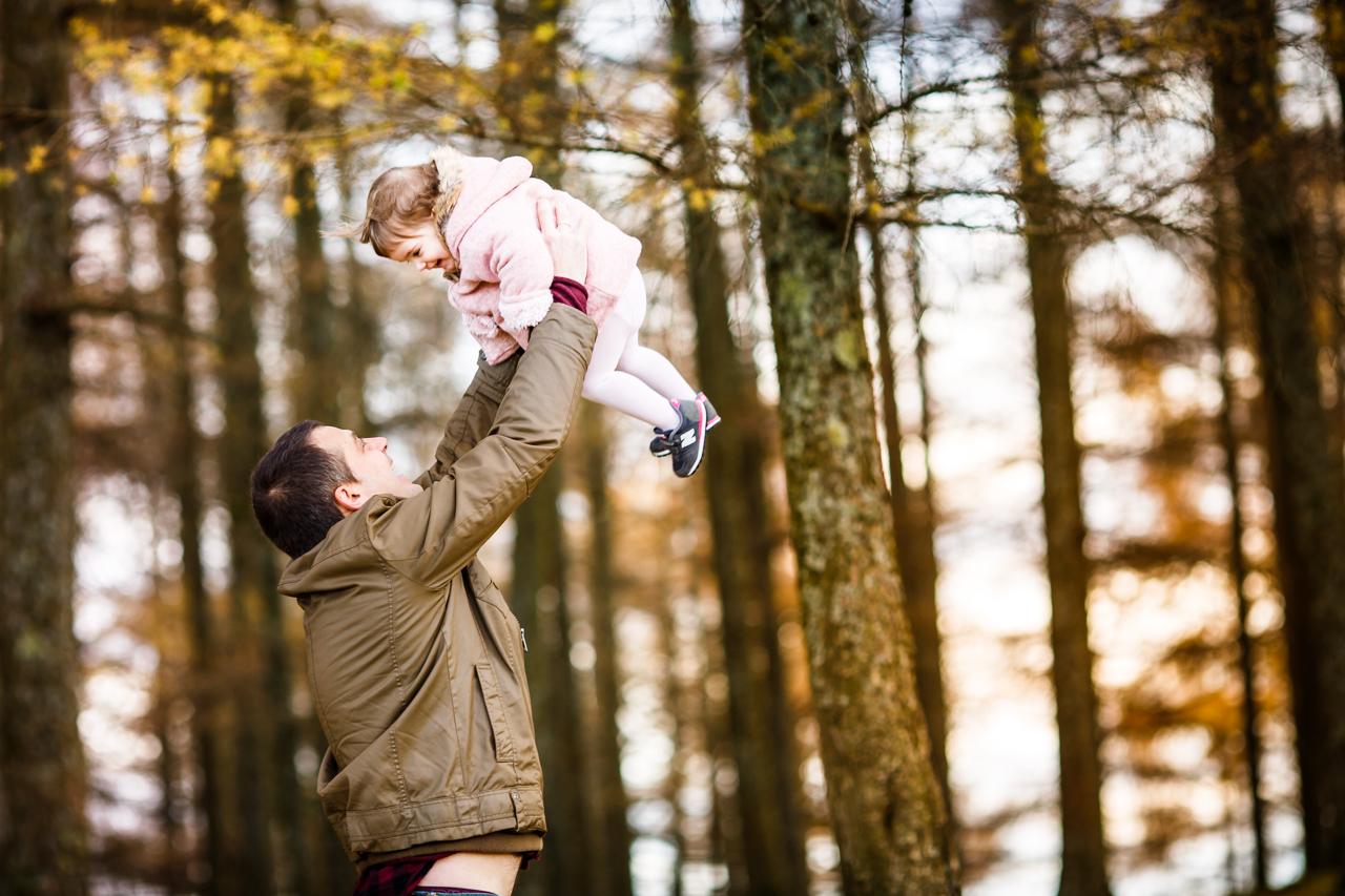padre alzando en brazos a su hija en un reportaje de familia en el monte de erlaitz