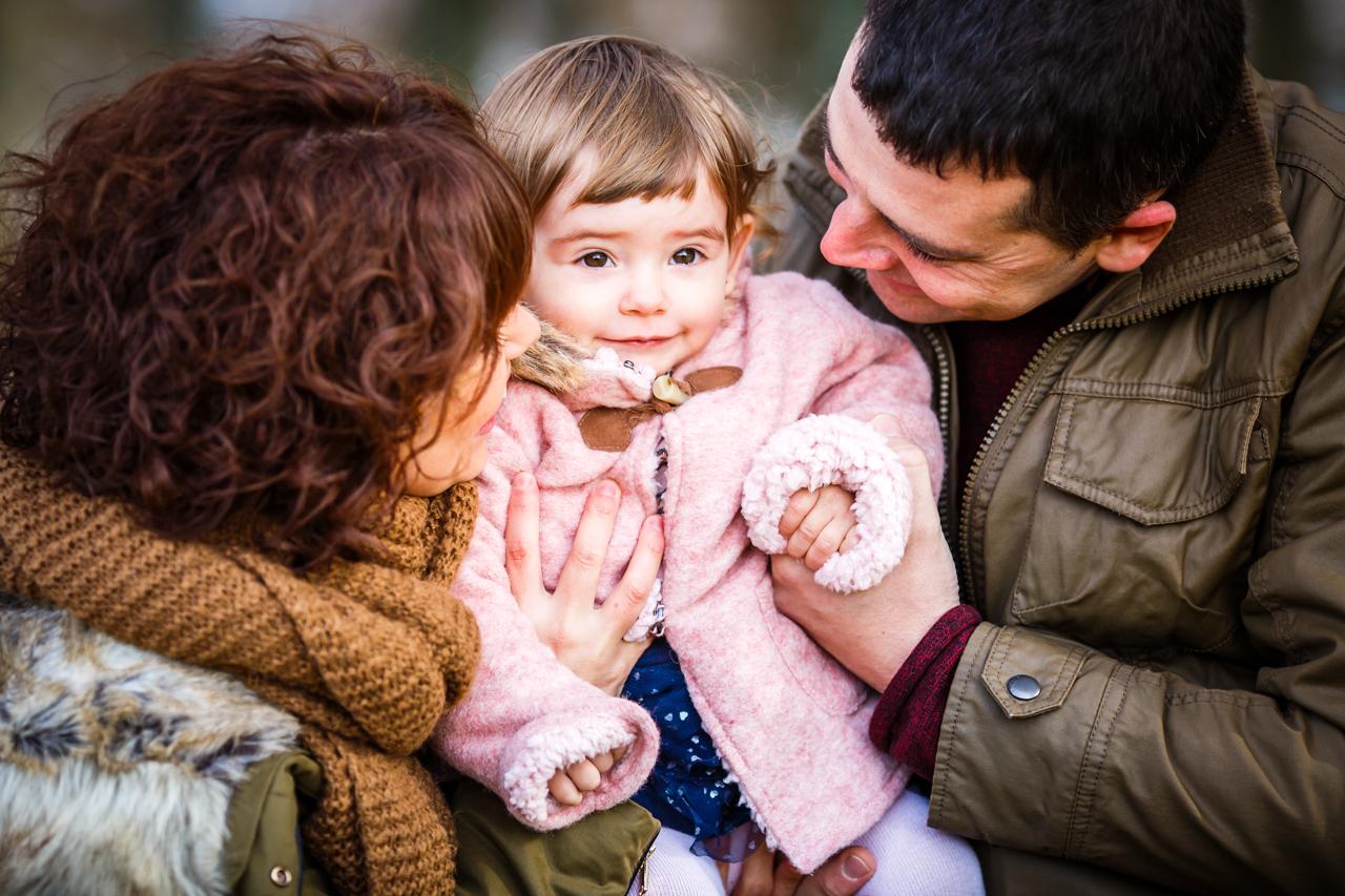 padres mirando a su pequeña enamorados de ella en un reportaje de familia en gipuzkoa