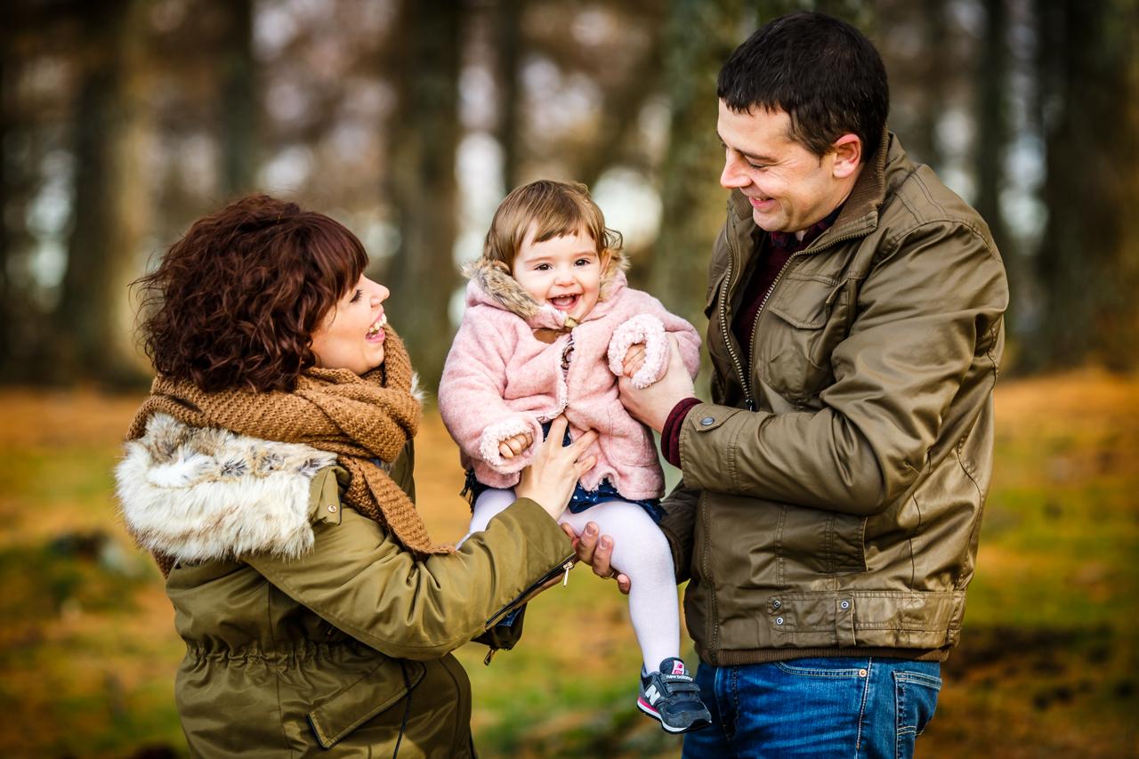 pares felices sonriendo con su hija en brazos en un reportaje de familia en irun