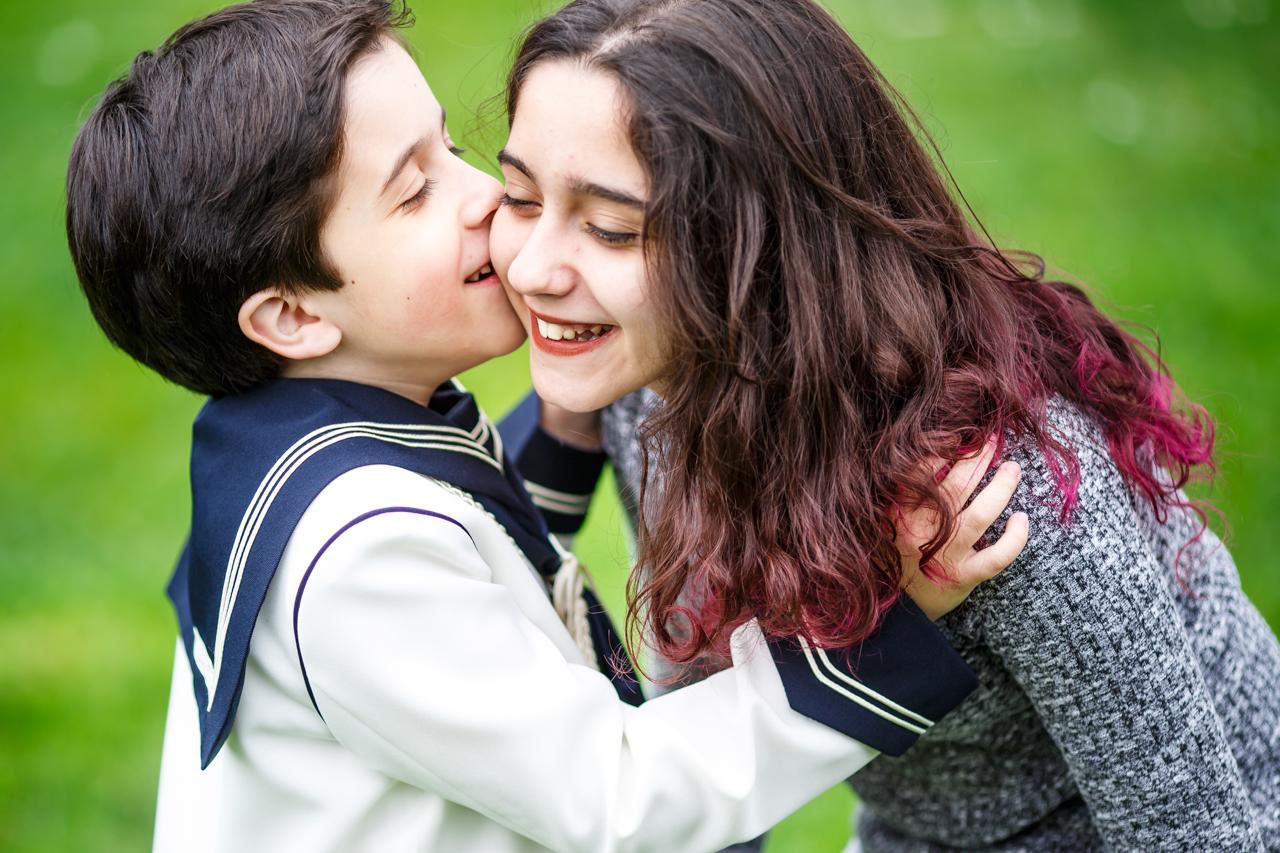 beso de un niño vestido de comunión a su hermana en un reportaje de comunión en hondarribia