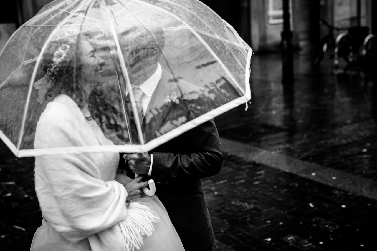 pareja de novios debajo de un paraguas transparente en un reportaje de boda en donostia
