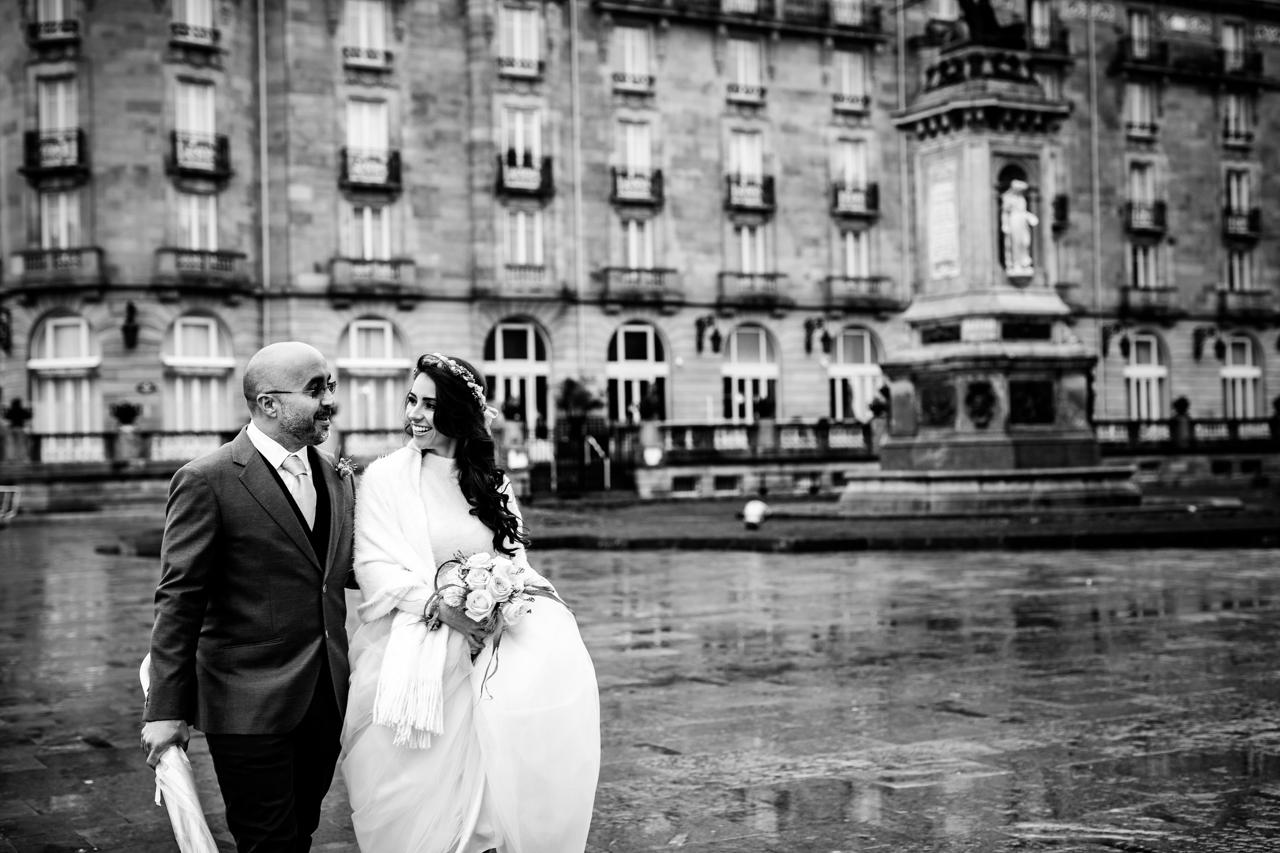 pareja de casados mirandose en las calles de san sebastian mojadas boda fotografos