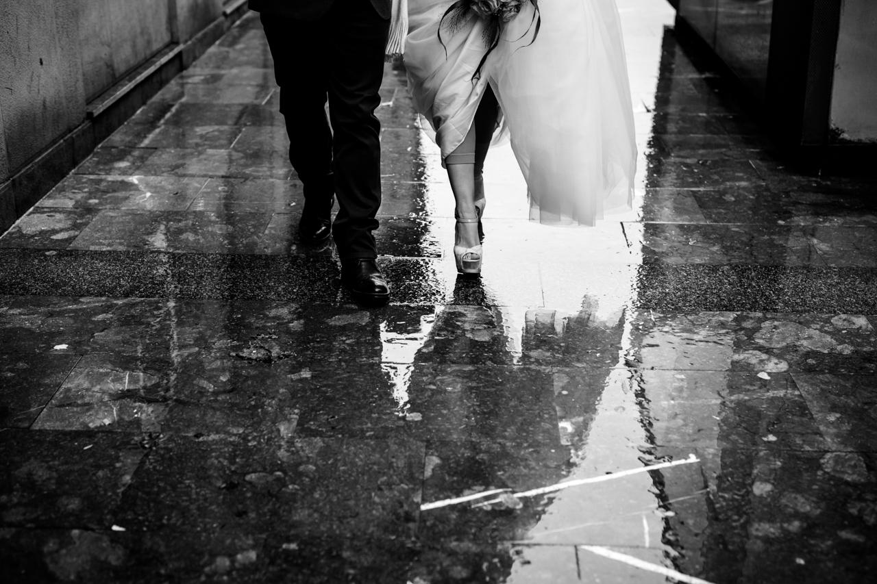 pareja de recien casados andando por las calles de san sebastian mojadas