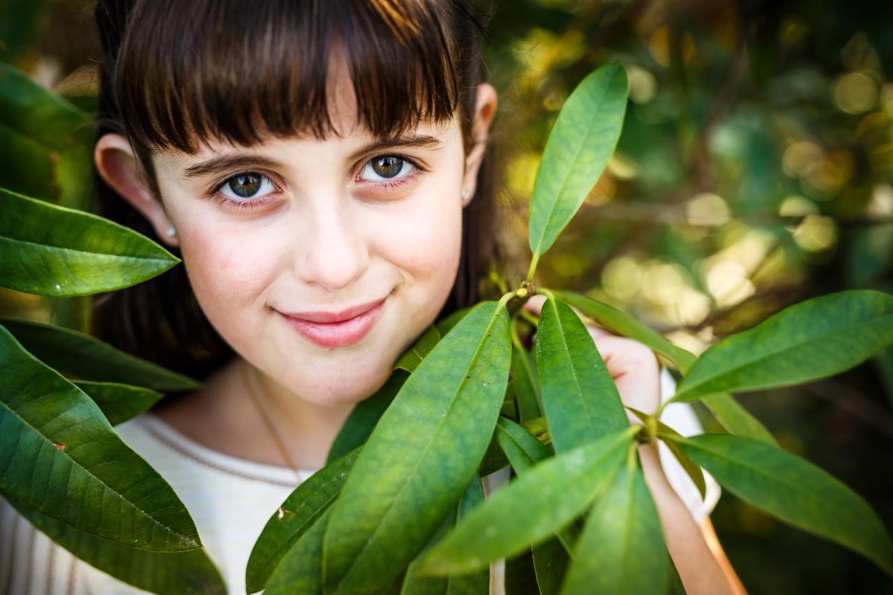 niña vestida de comunión entre ramas y con los ojos muy abiertos
