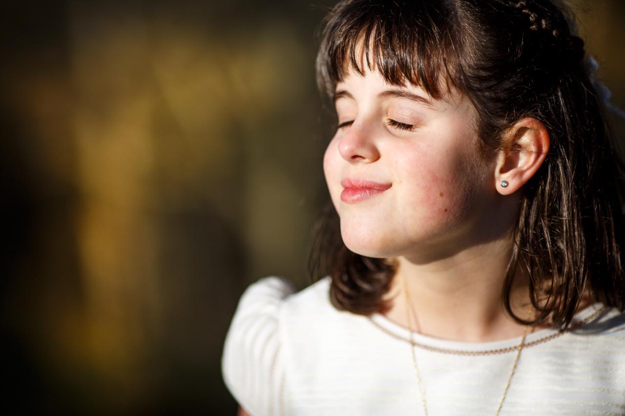 niña vestida de comunión con los ojos cerrados y sonriendo al cielo