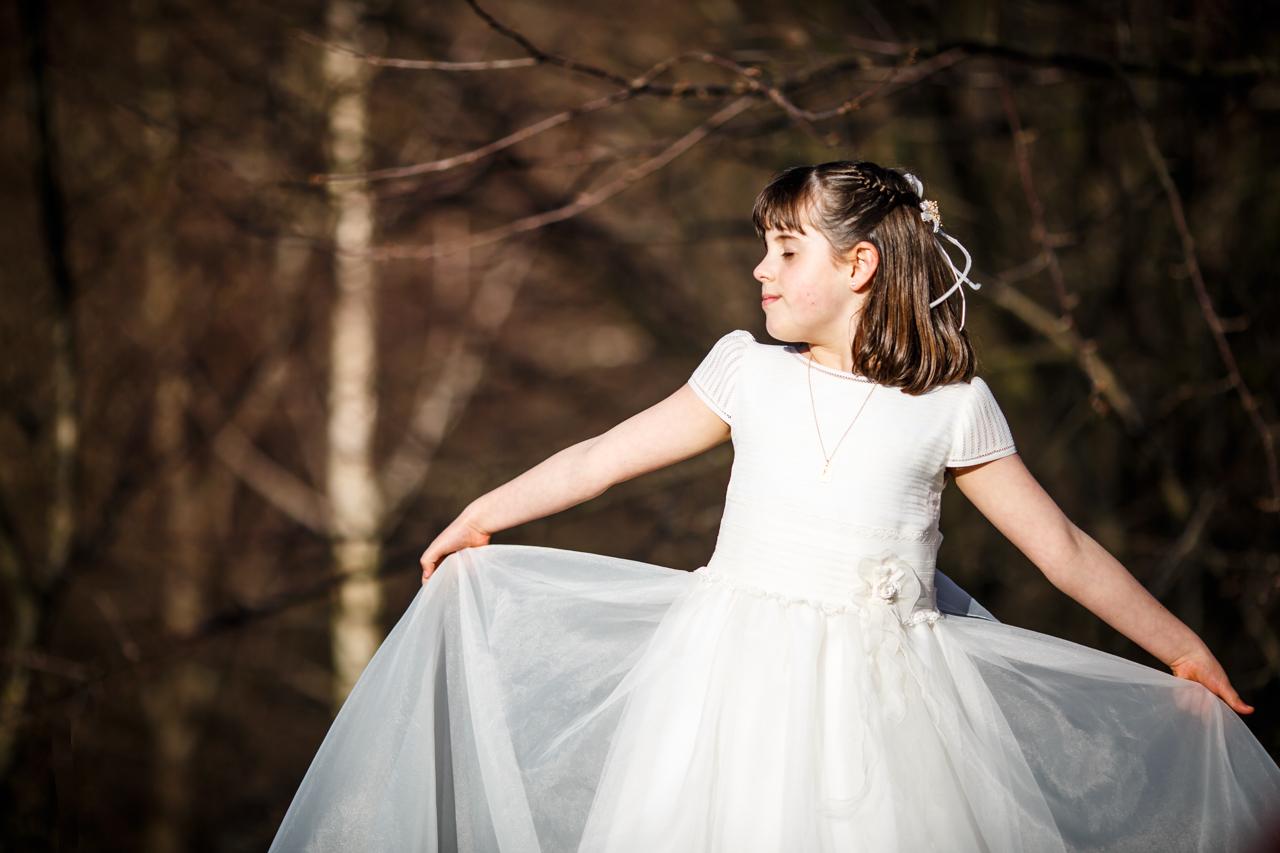 niña vestida de comunión agarrando el vestido con ojos cerrados