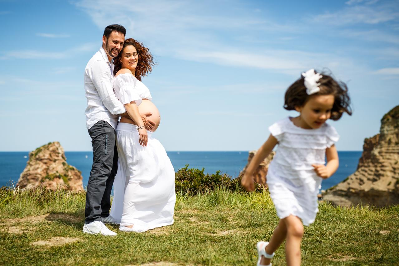 fotografía de pareja embarazada y su hija corriendo
