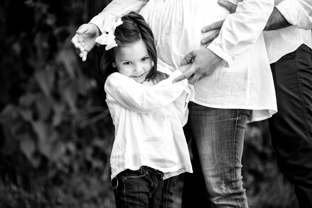 niña abrazada a la tripa de su madre embarazada