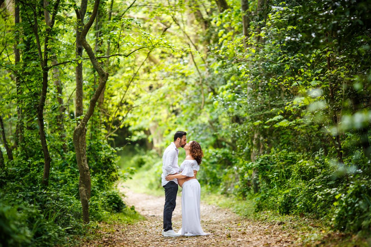 pareja de embarazo en un bosque verde precioso dandose un beso