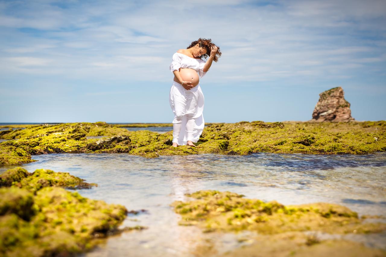 embarazada en la playa agarrándose el pelo en el agua