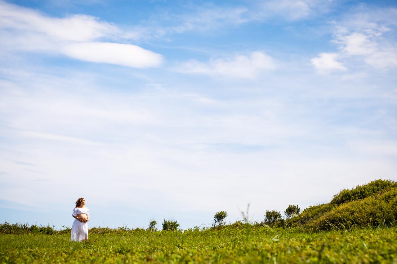 retrato de una mujer embarazada en una ladera verde fotografos
