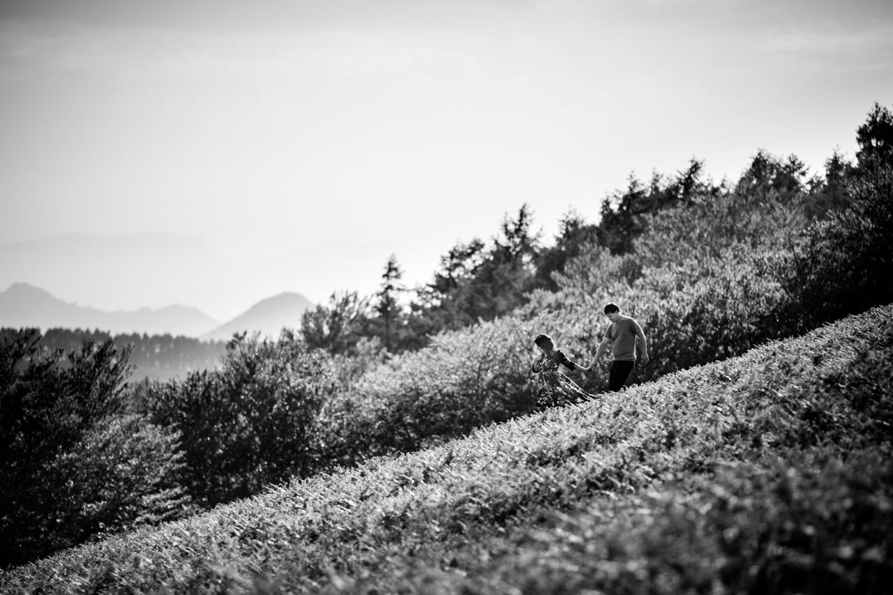 novios andando y bajando una ladera de oinaleku en una preboda en oiartzun