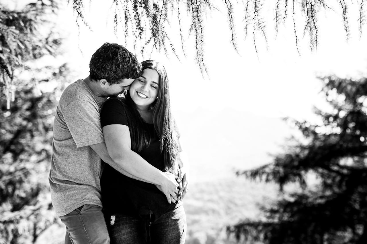 abrazo del chico a su chica y beso en la mejilla en un reportaje de pareja en erlaitz