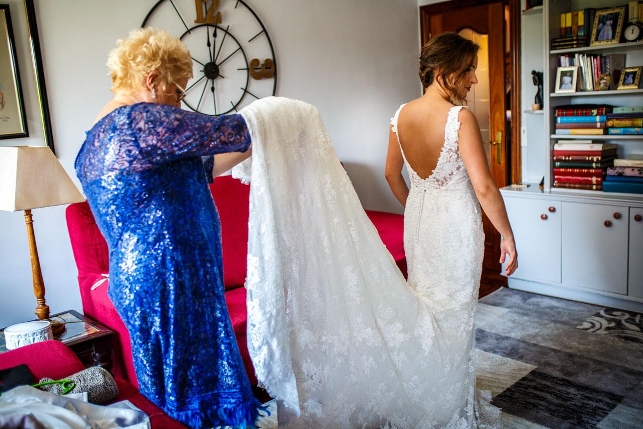 la madre de la novia colocando bien el vestido a la novia en una boda en guadalupe