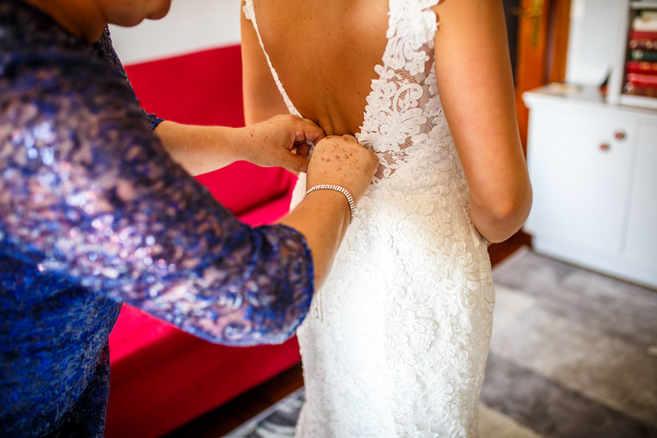 la madre de la novia atando el vestido a la novia en una boda en guadalupe