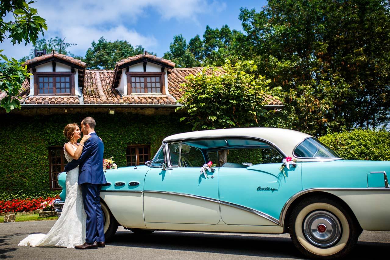 los novios abrazados delante del coche de la novia en una boda en guadalupe