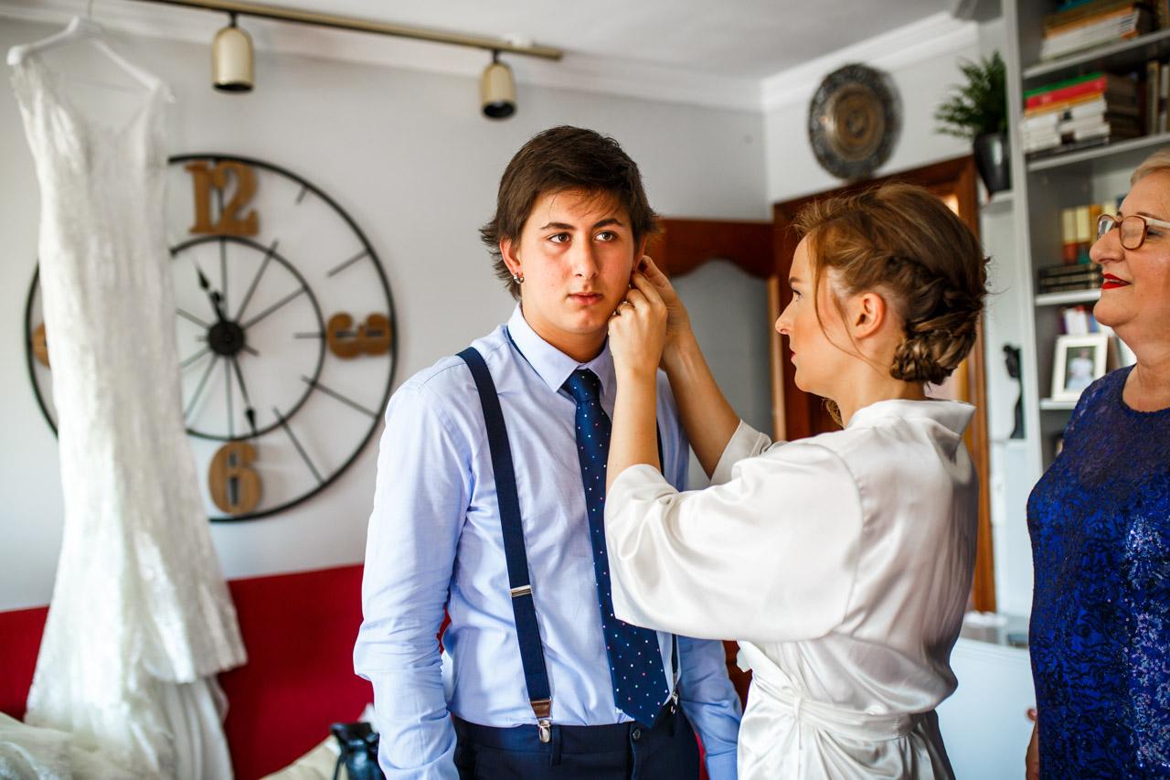 la novia poniendo el pendiente a su hermano en una boda en guadalupe
