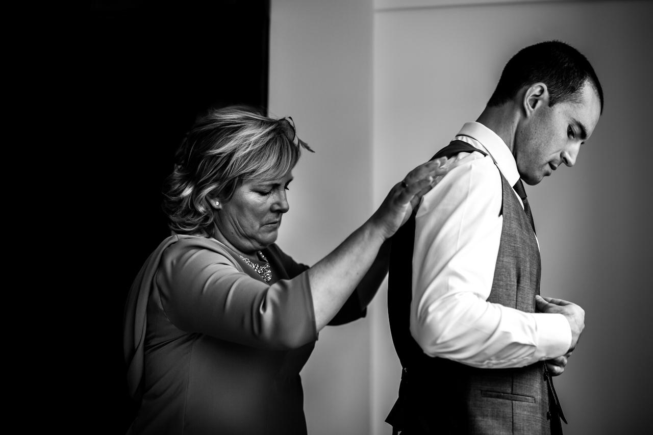 el novio vistiéndose con la ayuda de su madre en una boda en guadalupe