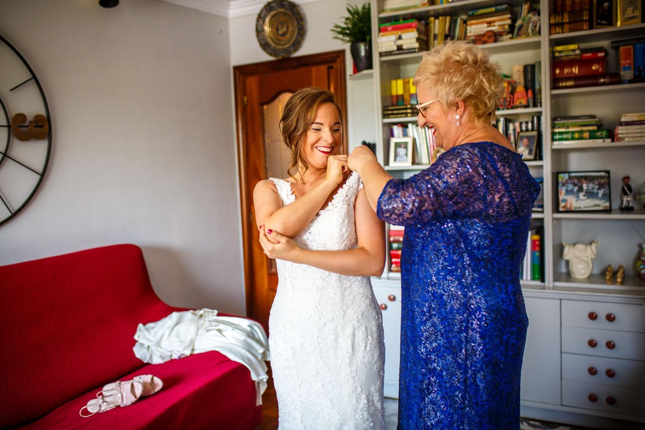 la madre de la novia vistiendo a la novia en una boda en guadalupe