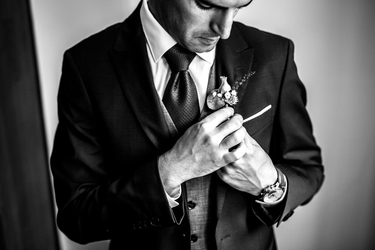 el novio mientras se pone el prendido en una boda en guadalupe