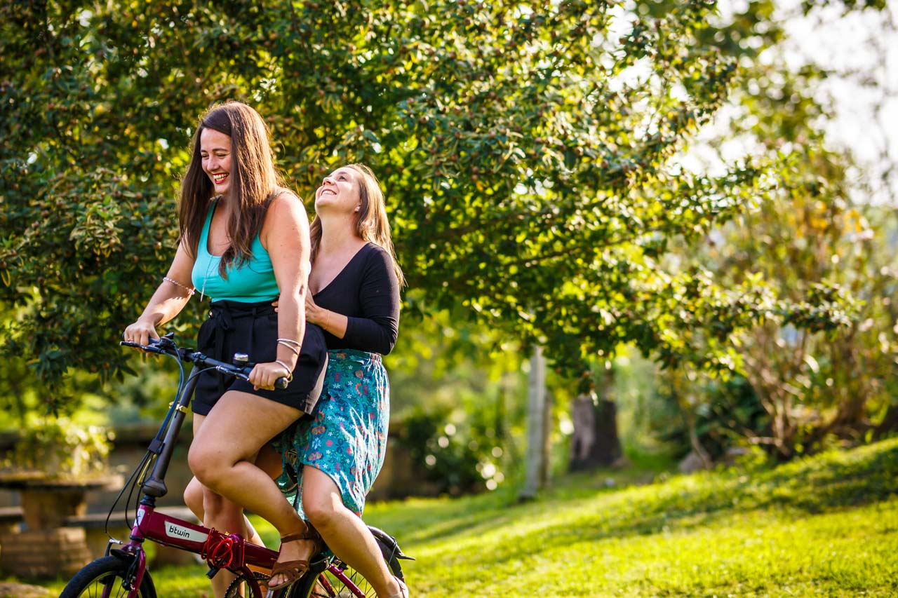 las novias se ríen mientras andan en bici en una preboda en oiartzun