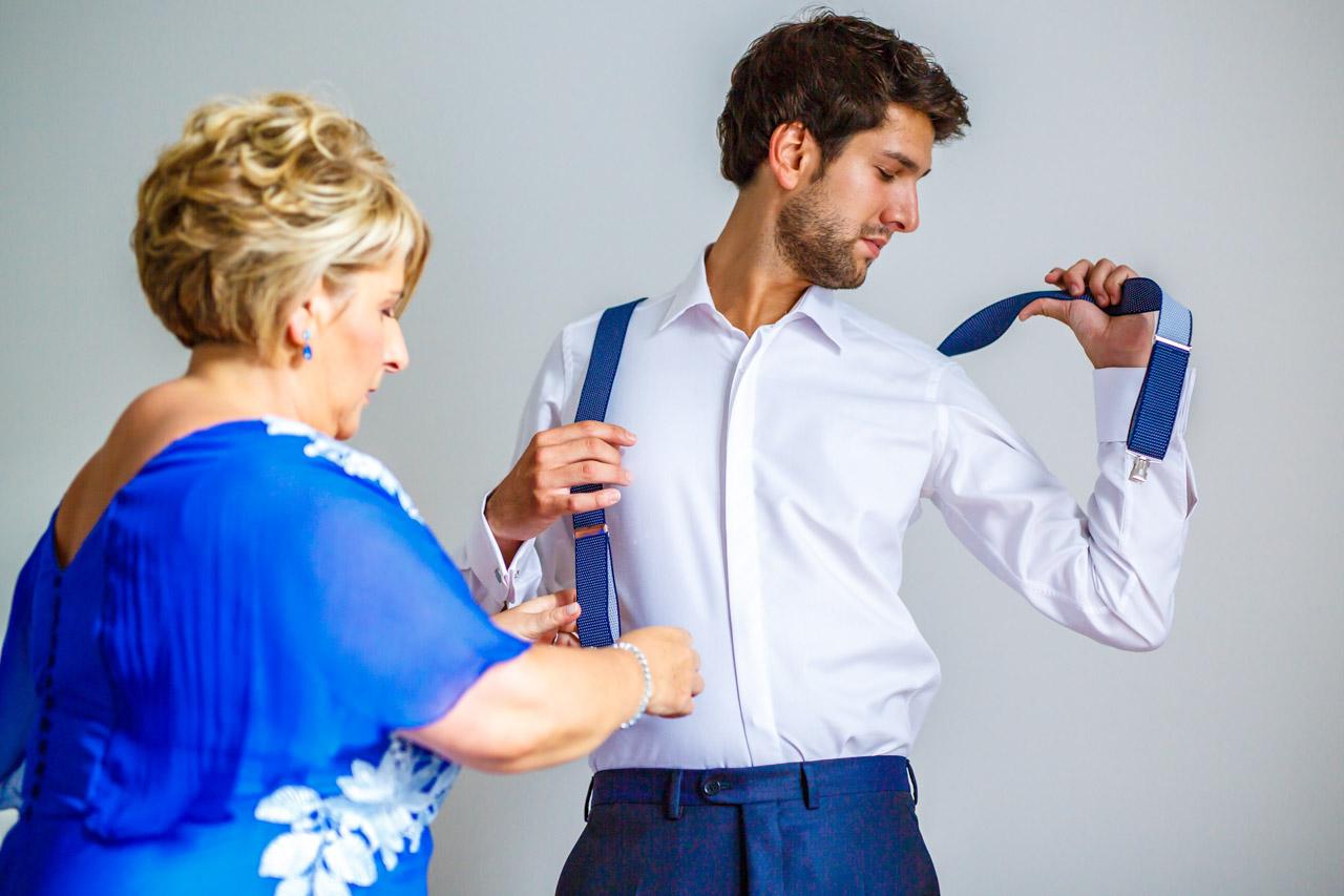 la tía ayuda al novio con los tirantes en una boda en irun