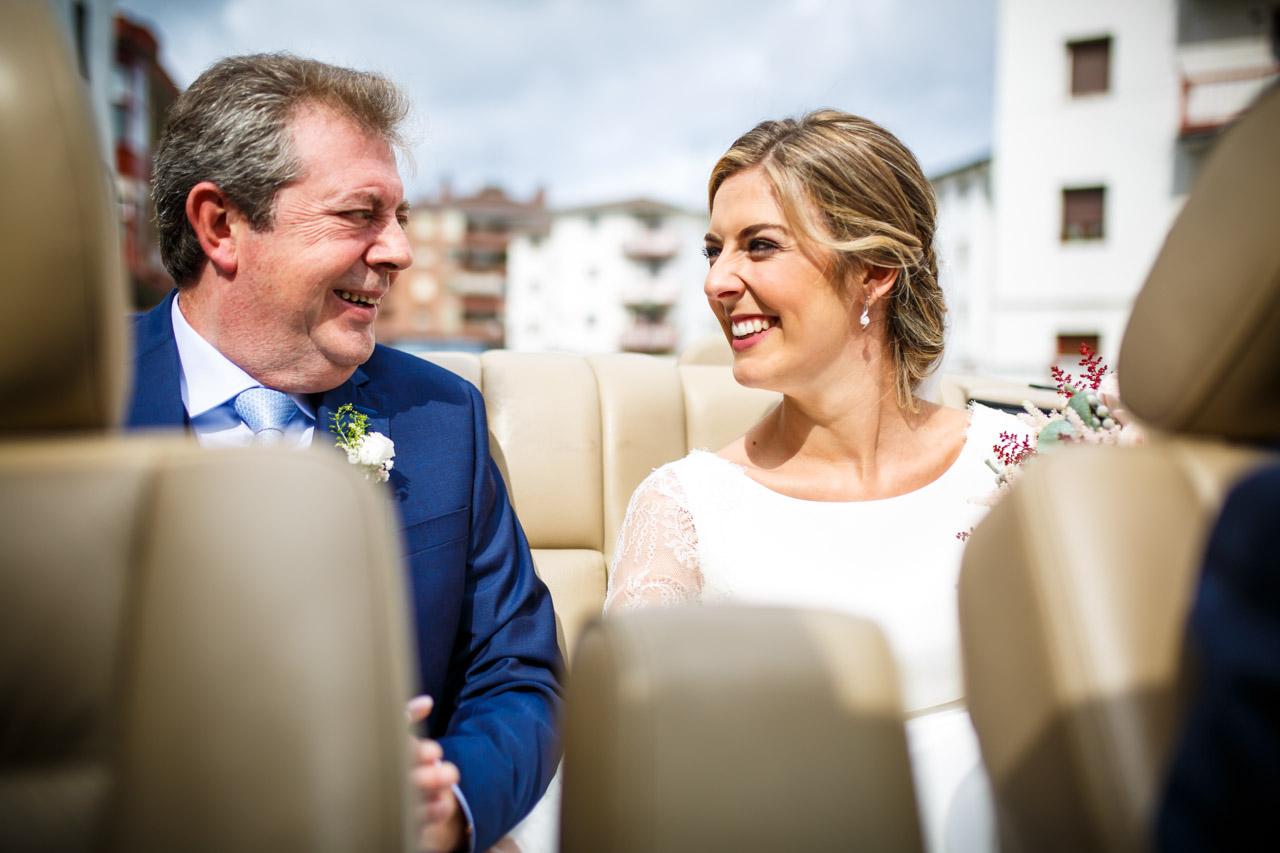 la novia sonríe junto con su padre mientras van en coche hacia la iglesia en una boda en irun