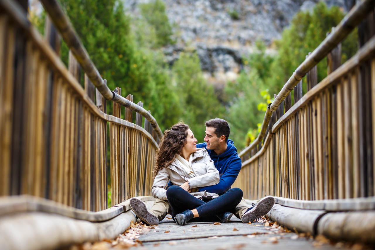 los novios sentados en un puente de la fuentona en una preboda en Soria