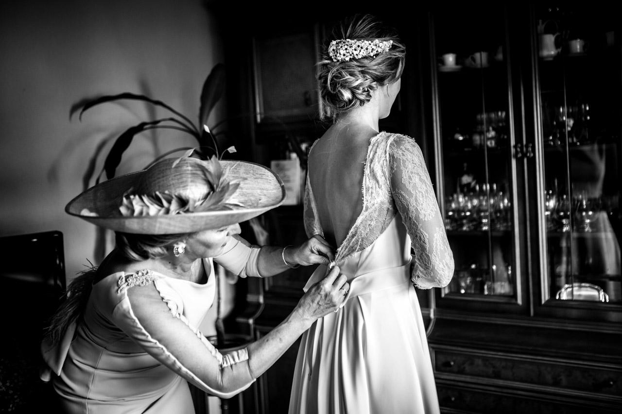 la madre ata el vestido a la novia en una boda en irun