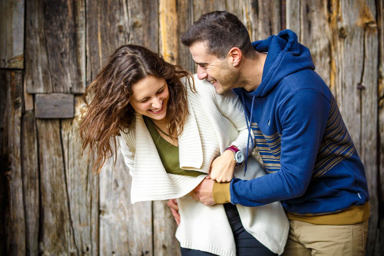 el novio haciéndole cosquillas a la novia delante de una puerta de madera en una preboda en Soria