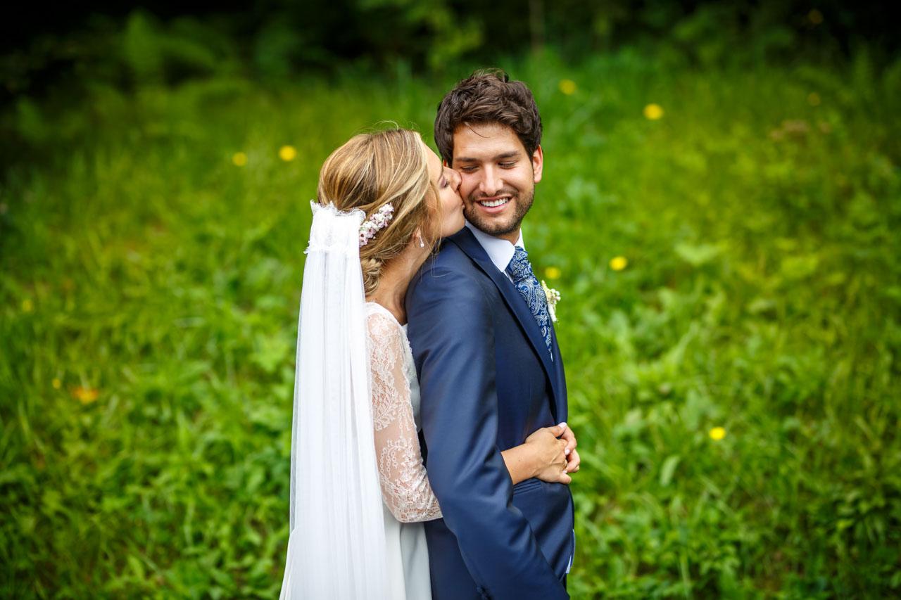 la novia besa al novio durante el reportaje de fotos en una boda en el real club golf de san sebastian