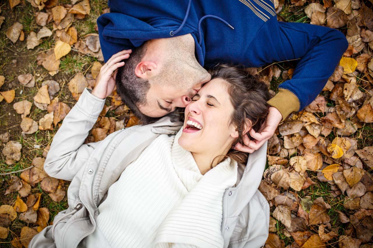 Los novios tumbados sobre hojas caídas por el otoño en una preboda en Soria
