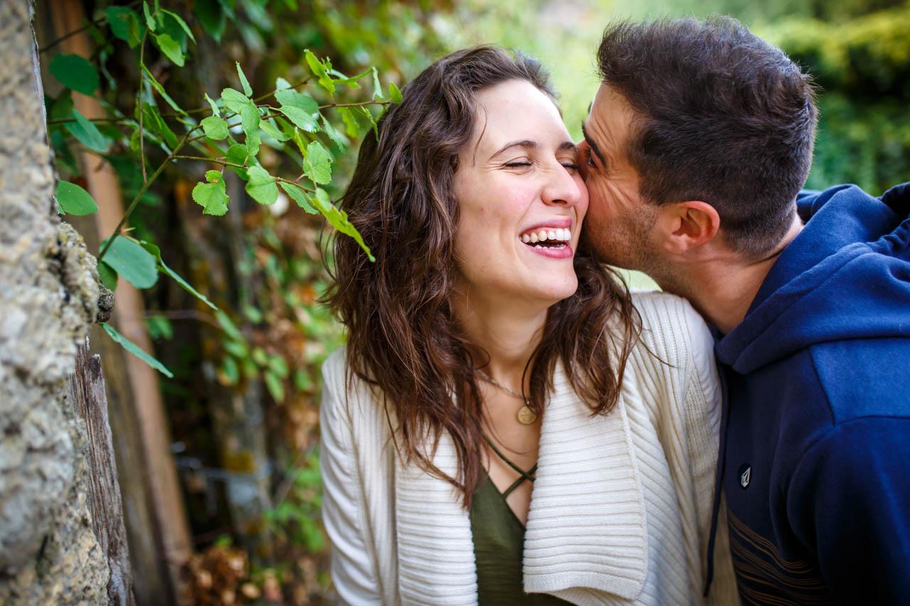 El novio susurrando algo gracioso a la novia en un rincón de Calatañazor en una preboda en Soria