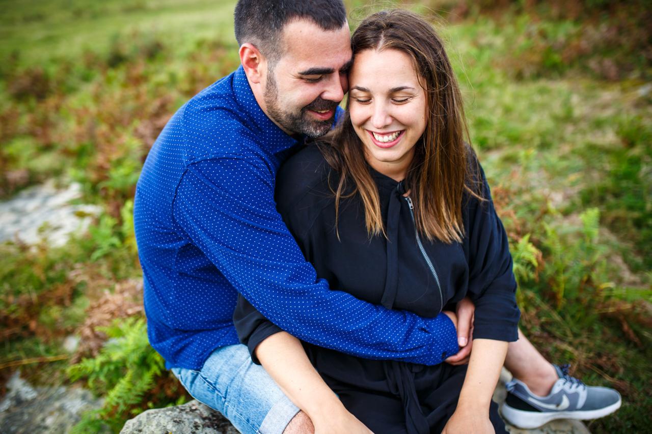abrazos sentados en una piedra pareja monte