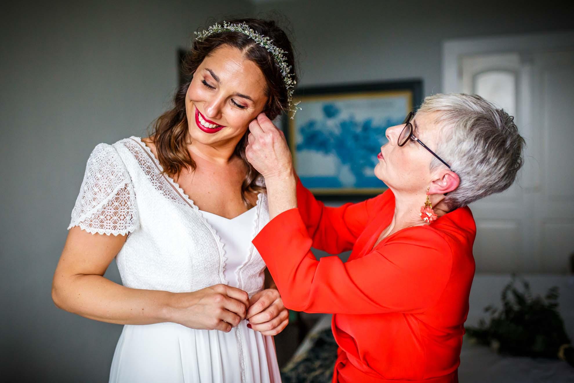 madre abrocha un pendiente a su hija