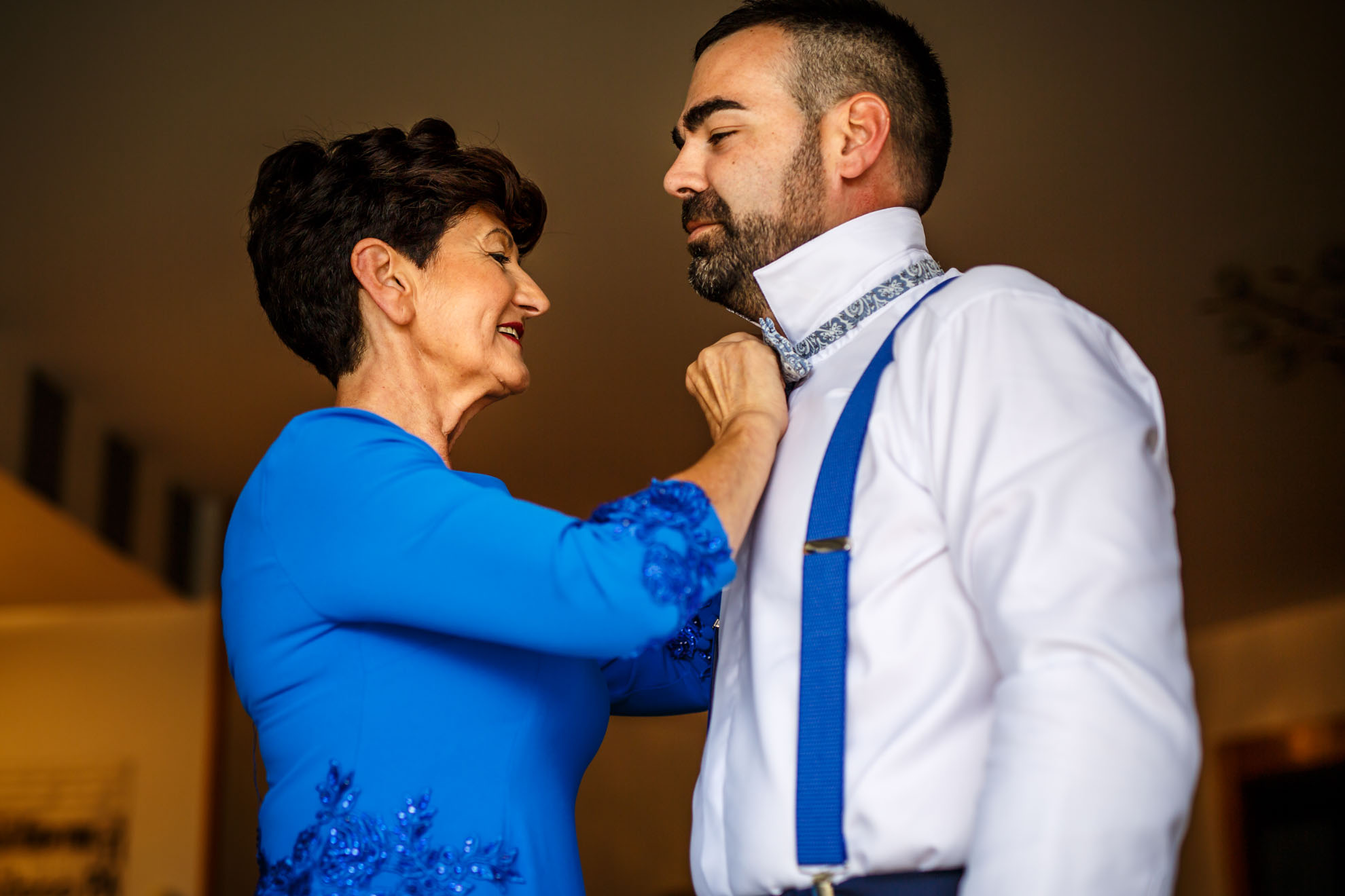 madre le abrocha la camisa y pajarita a su hijo
