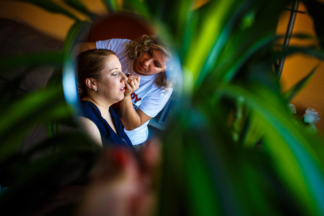 amiga maquillando a la novia en un reflejo de espejo