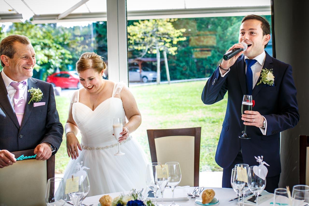 novios hablando por micrófono y la novia junto con los invitados a carcajadas